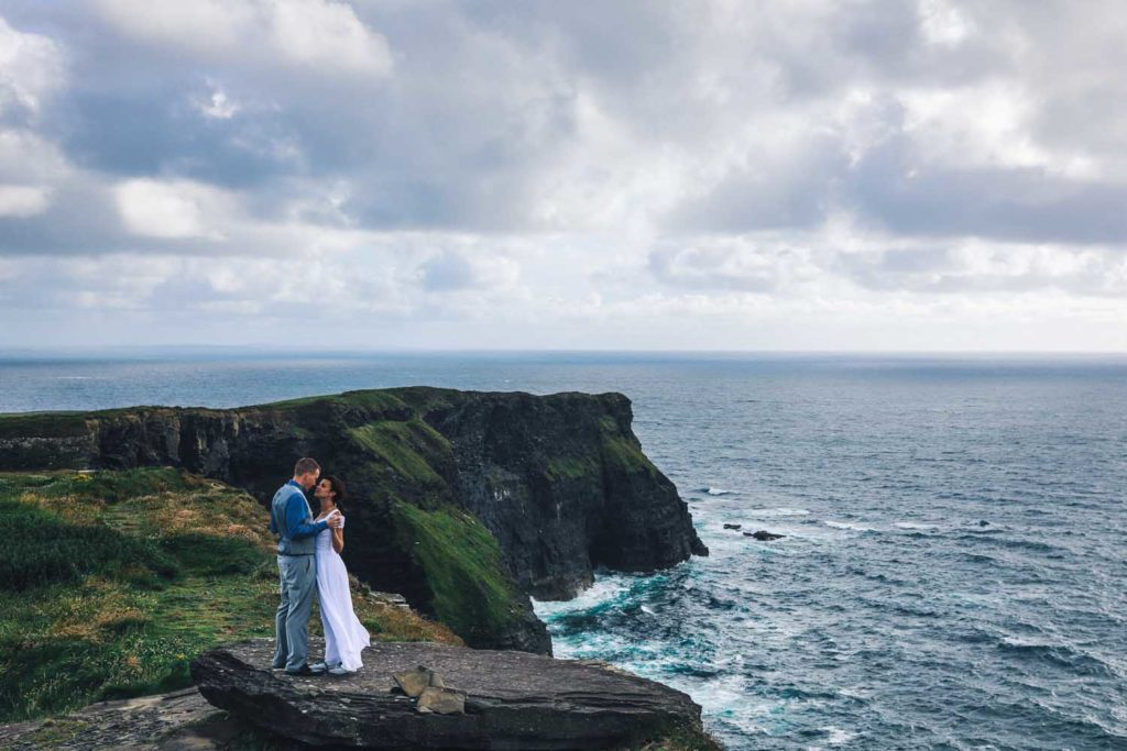 Married couple embrace at the Cliffs of Moher