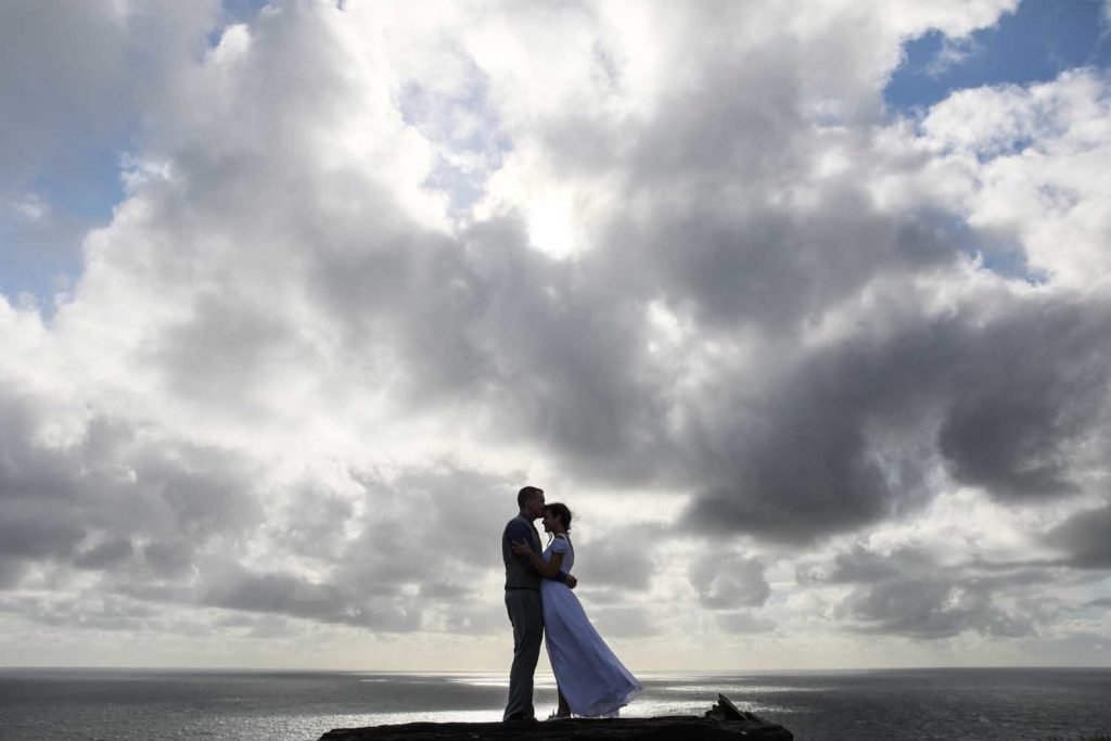 Couple embrace on the cliff's edge during their elopement at the Cliffs of Moher