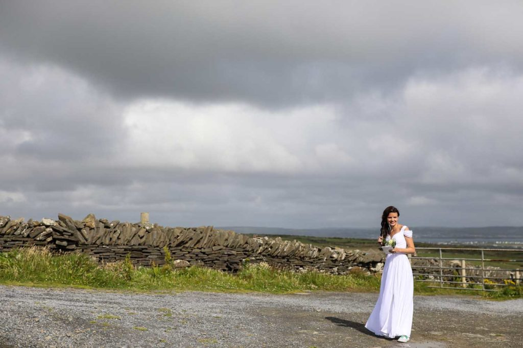 Bride standing against the irish countryside