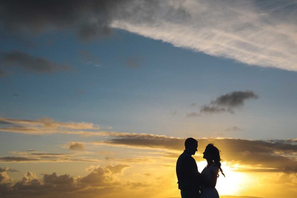 Couple embrace with the open sky in the background