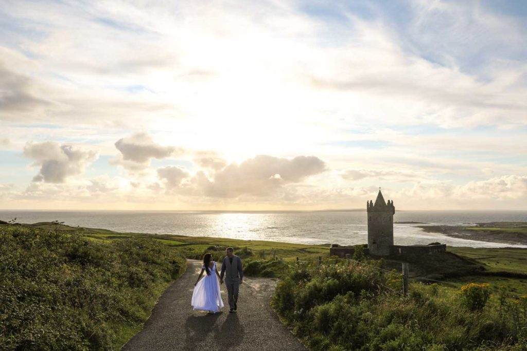Married couple walking by Doonagore Castle, Co. Clare, Ireland