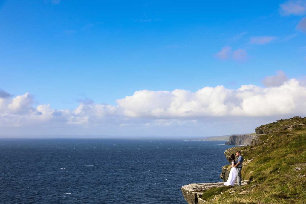 Married couple standing at the edge of a cliff, Co. Clare, Ireland