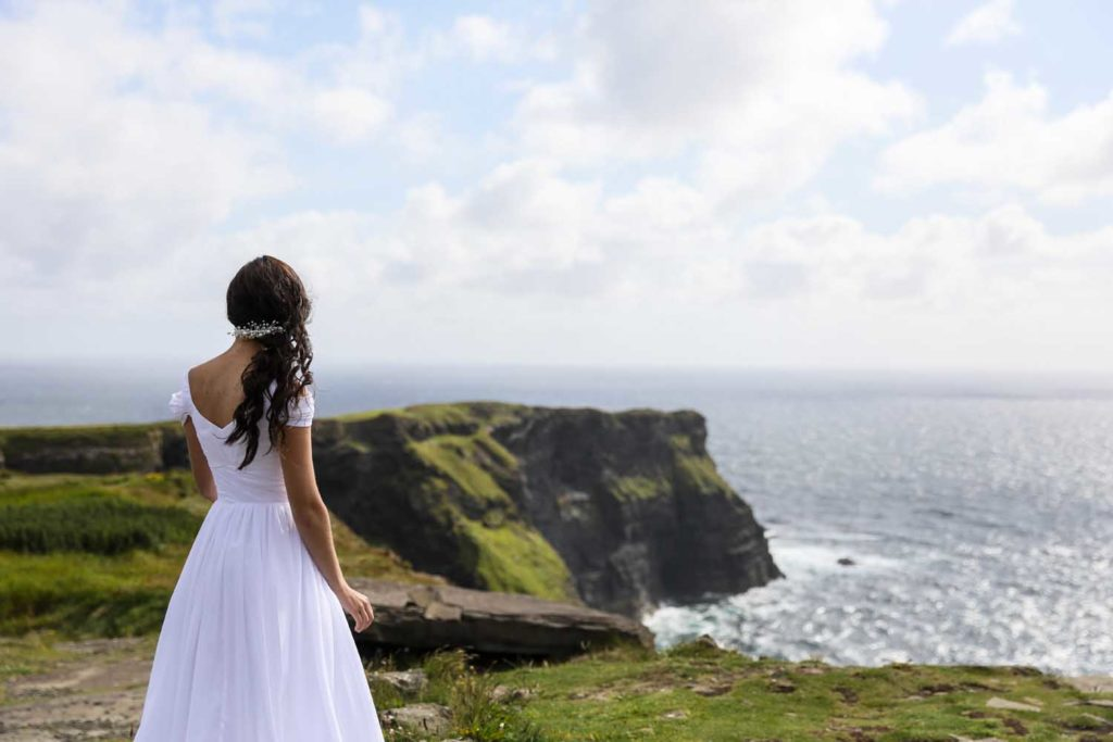 Bride looks out at the Atlantic Ocean on her wedding day