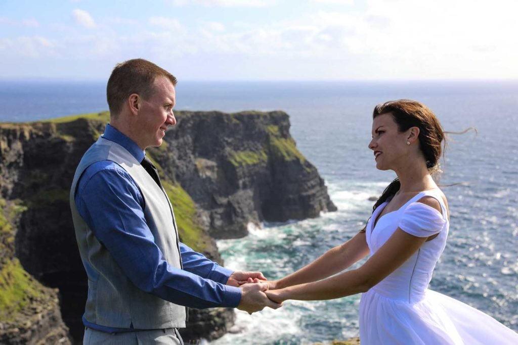 Holding hands during their wedding ceremony at The Cliffs of Moher