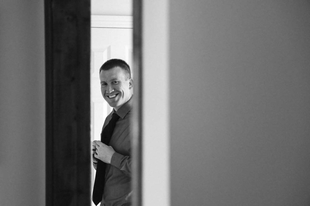 Groom photographed through a slightly ajar door