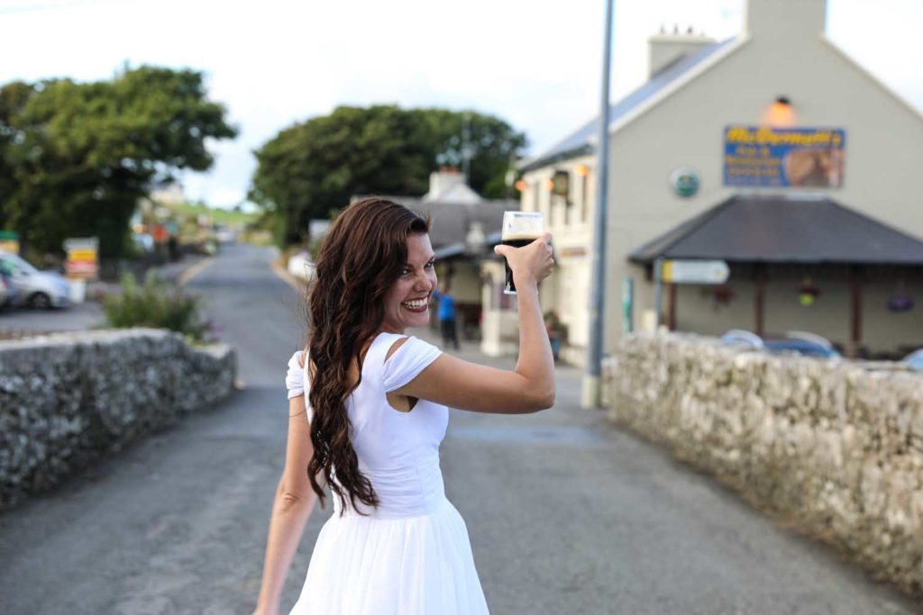 Bride carrying a Guinness in an irish village