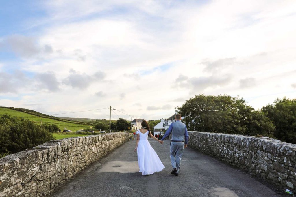 Newly married couple walking an irish country road