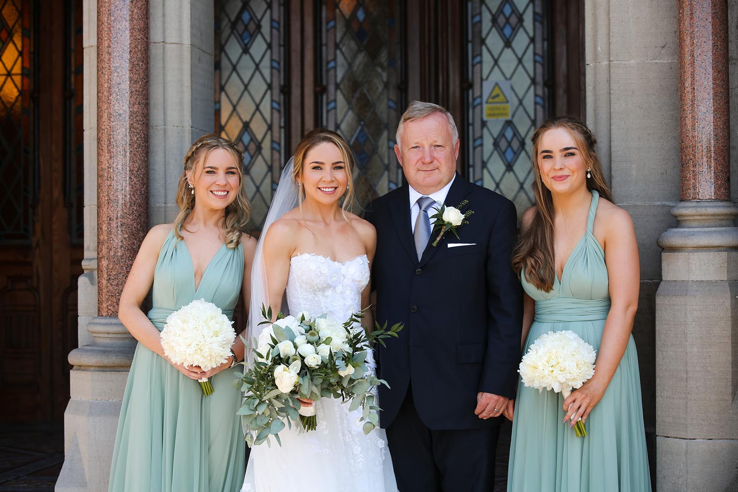 Bride with her father and bridesmaids on her wedding day