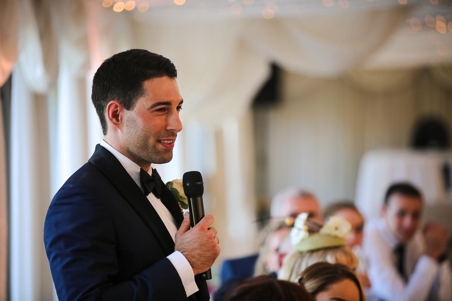 Groom smiling while making a speech on his wedding day
