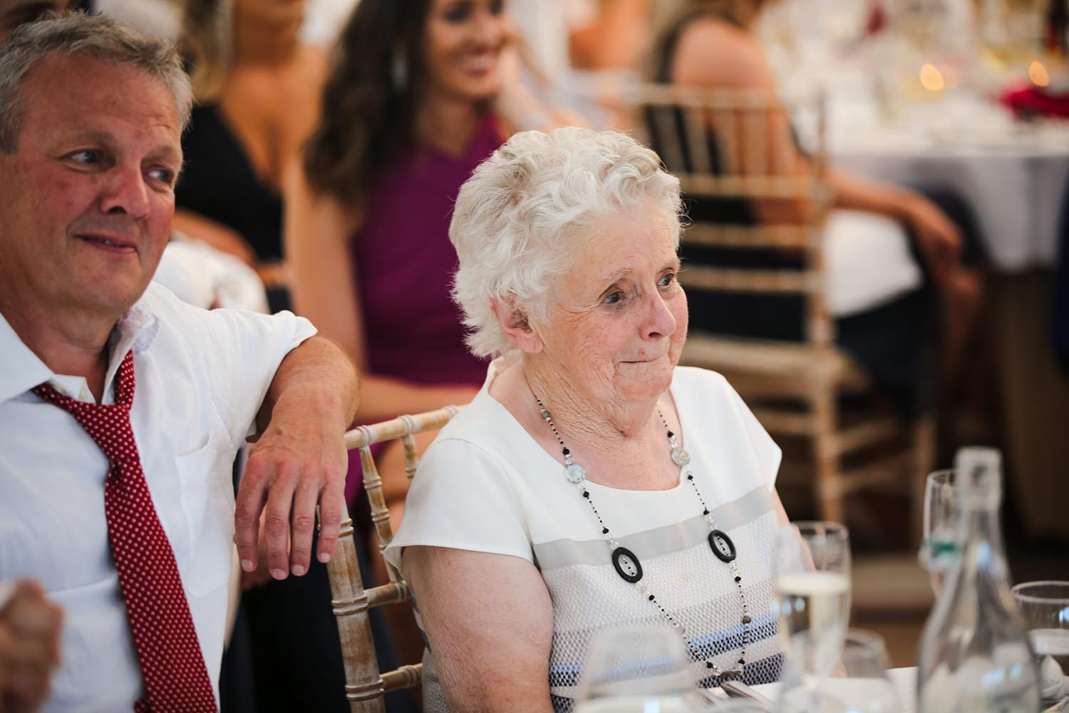 Elderly guests enjoying wedding speeches