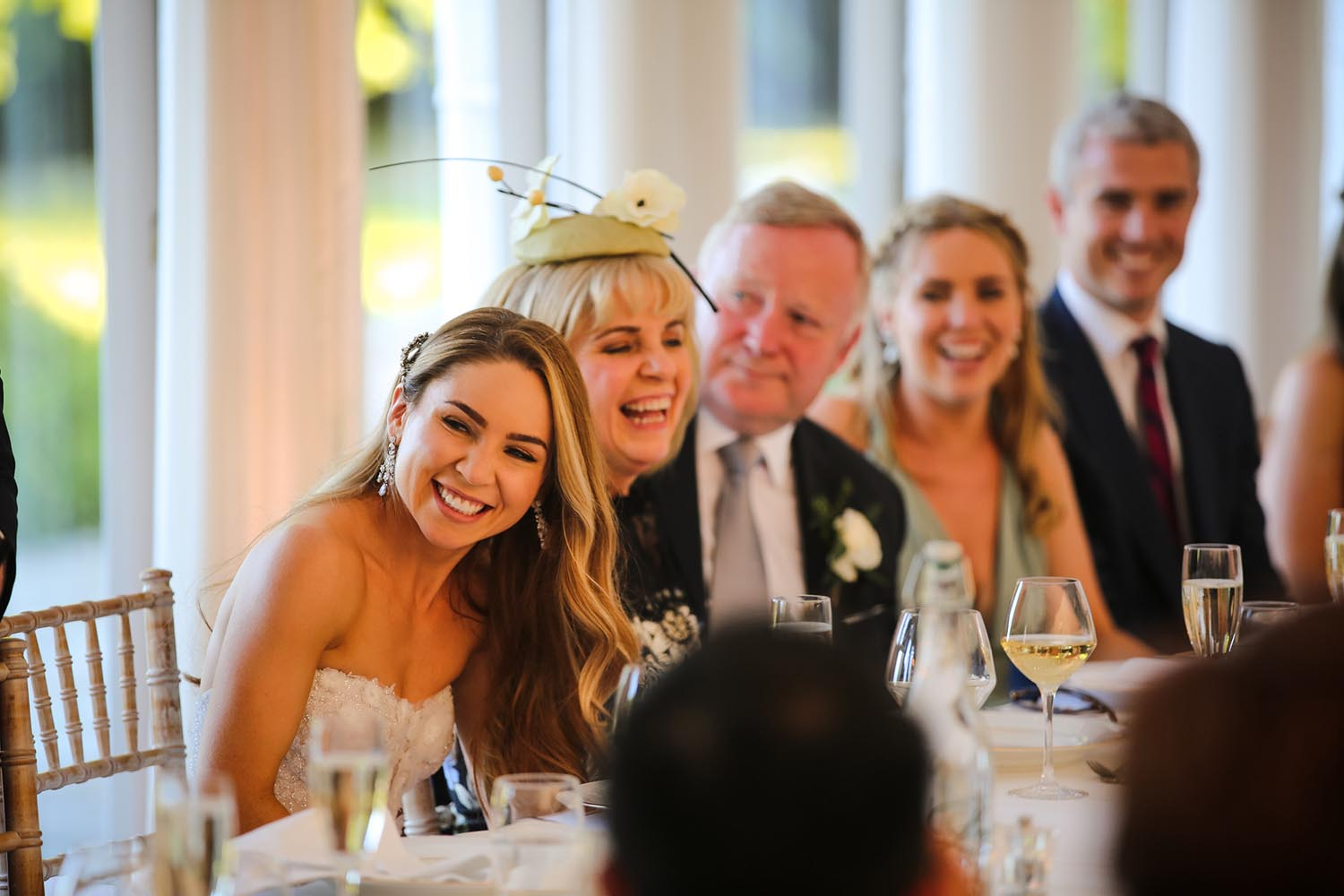 Bride and guests laughing during speeches