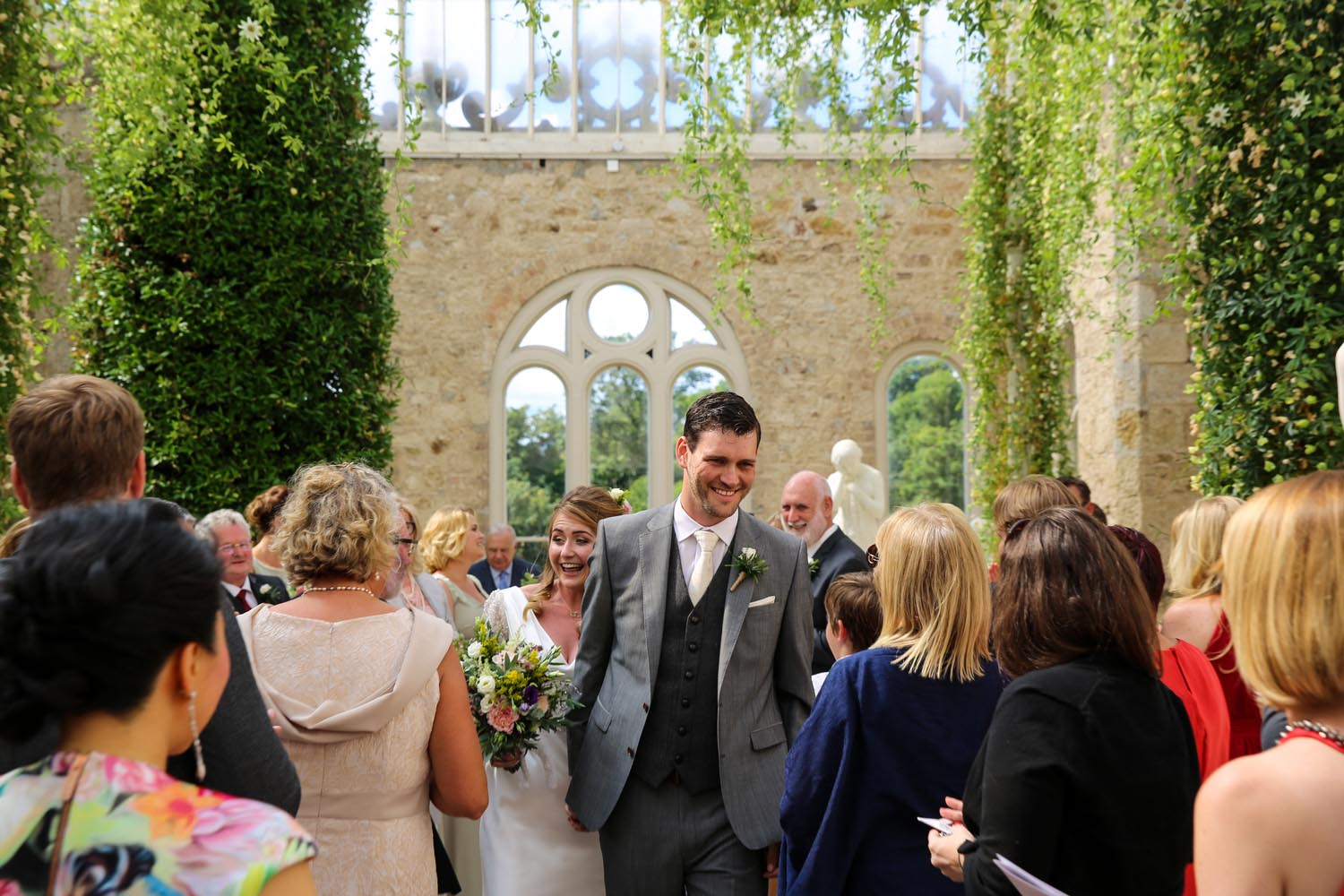 Bride and Groom greet guests in The Orangery