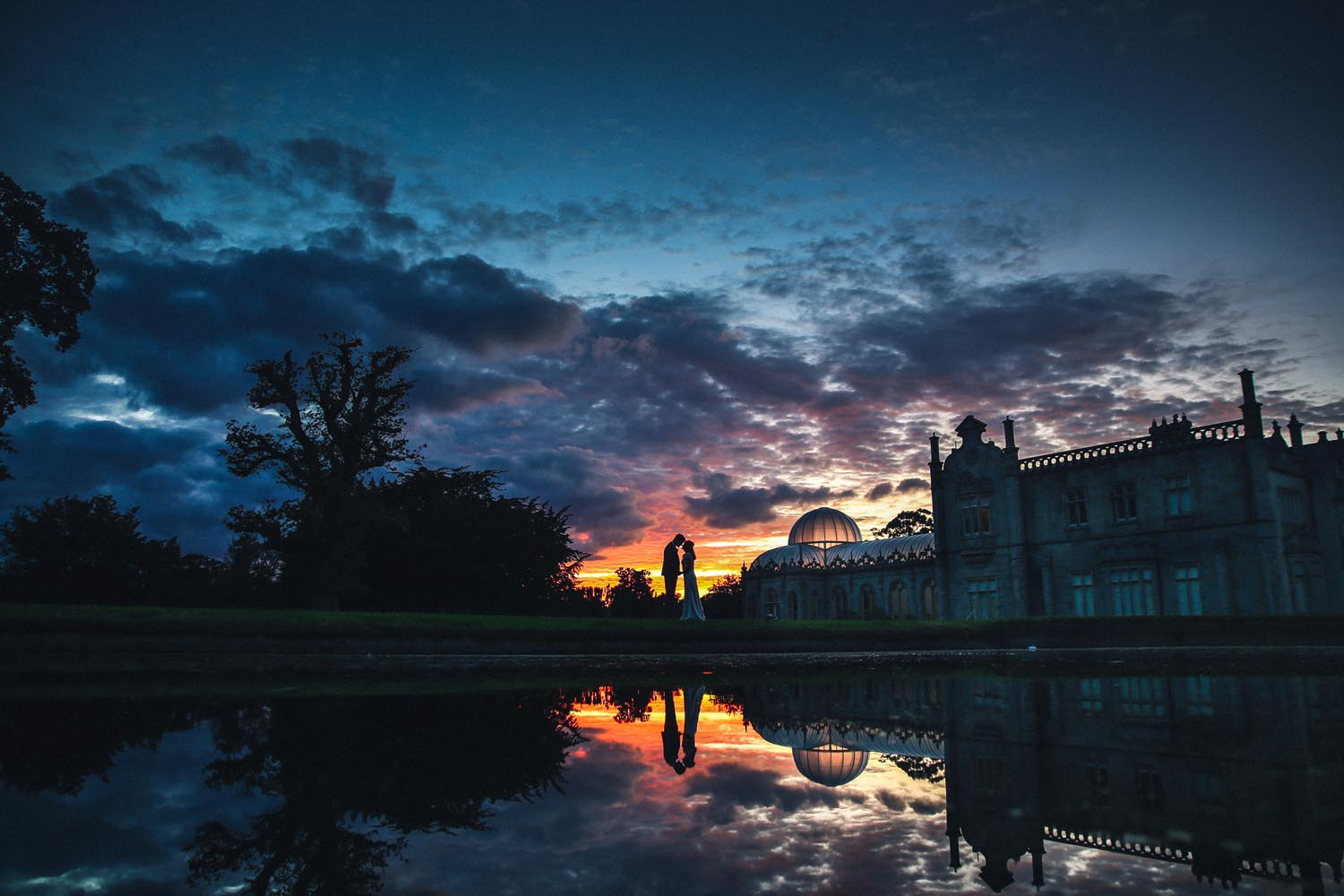 Married couple posing at sunset outside Killruddery House