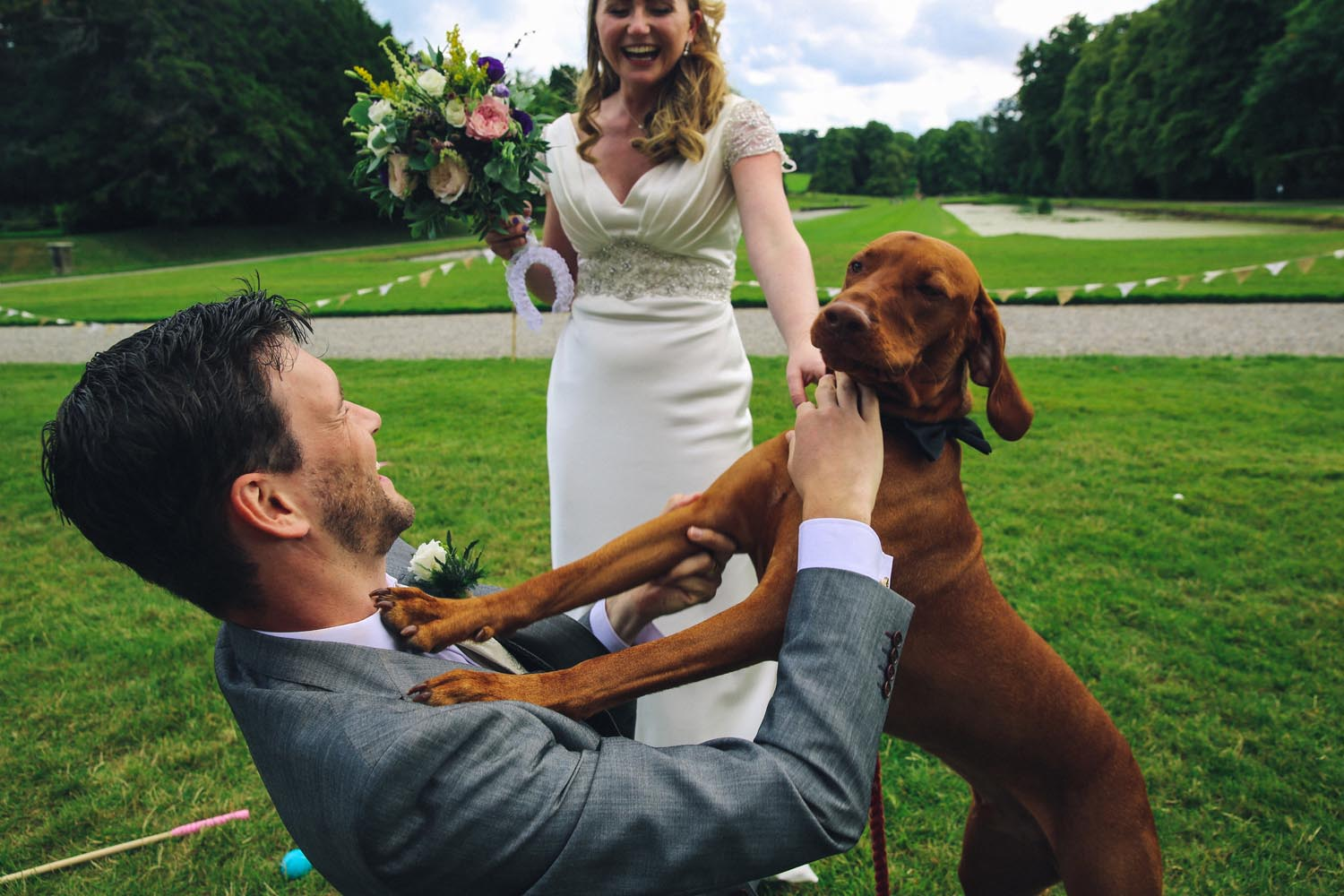 Couple and dog greeting each other after their wedding