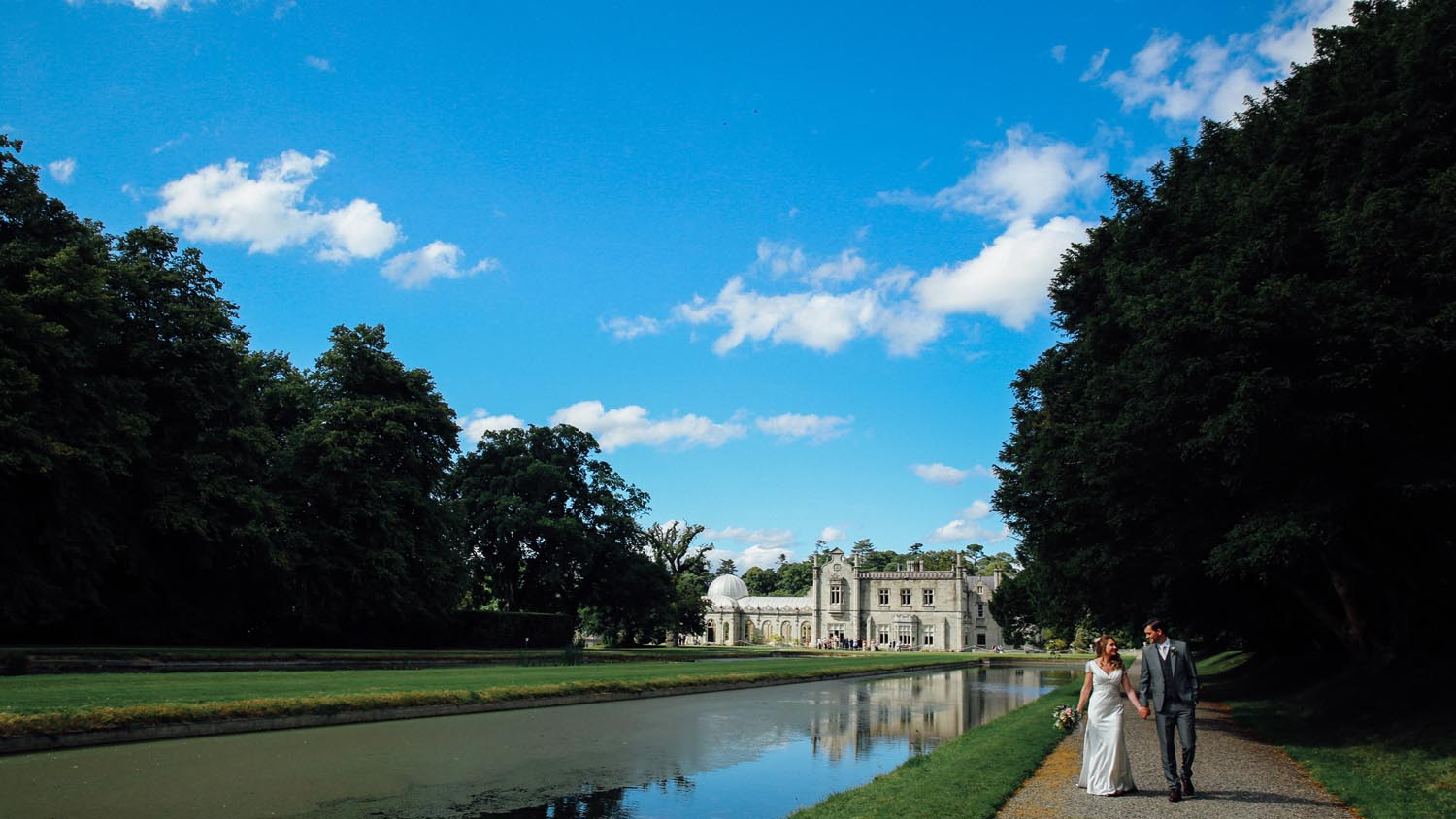 Couple strolling beside the lake with Killruddery House in the background