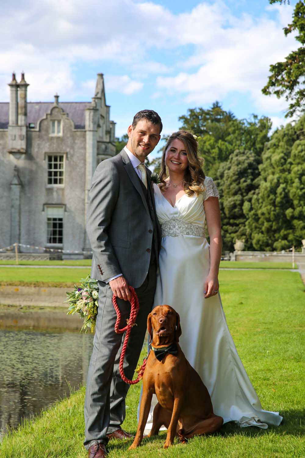 Couple photographed with their dog on their wedding day