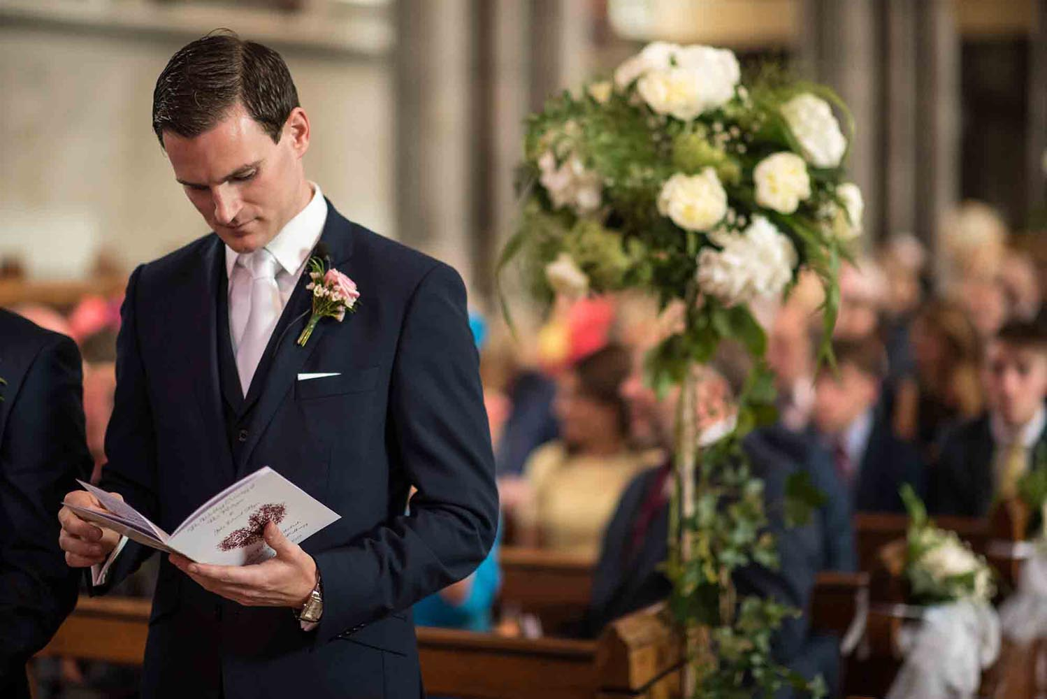Groom looking through wedding booklet at the church