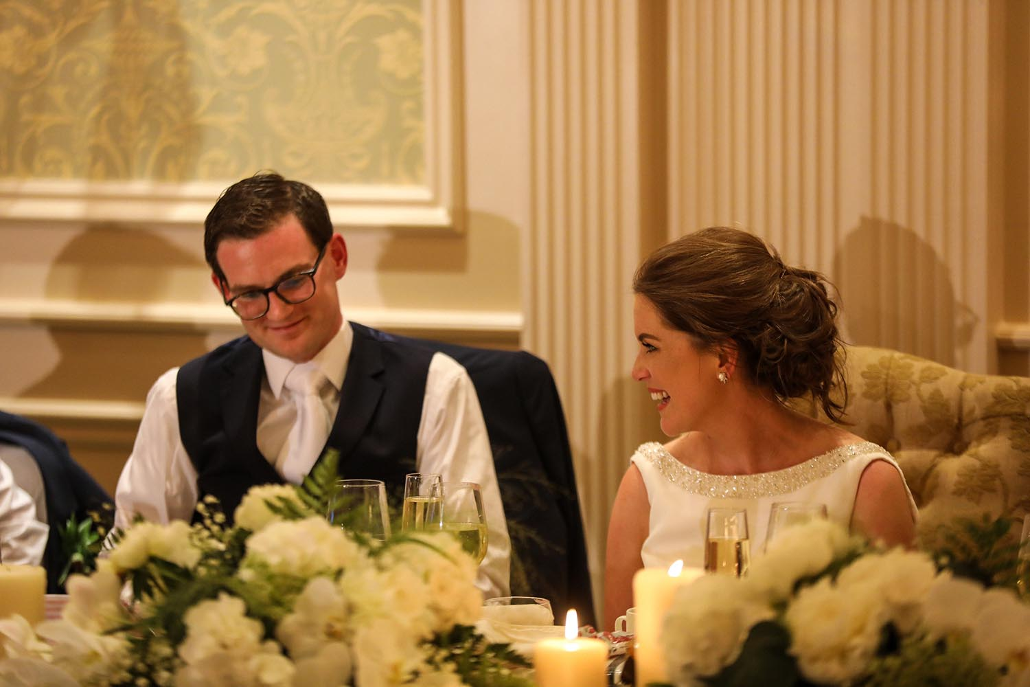 Couple smiling during their wedding meal