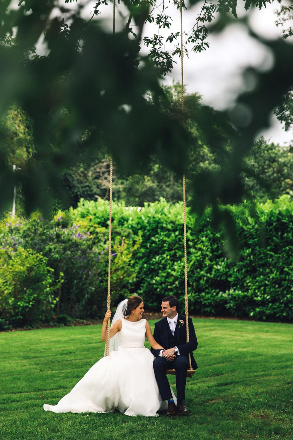 Newly married couple posing on a swing