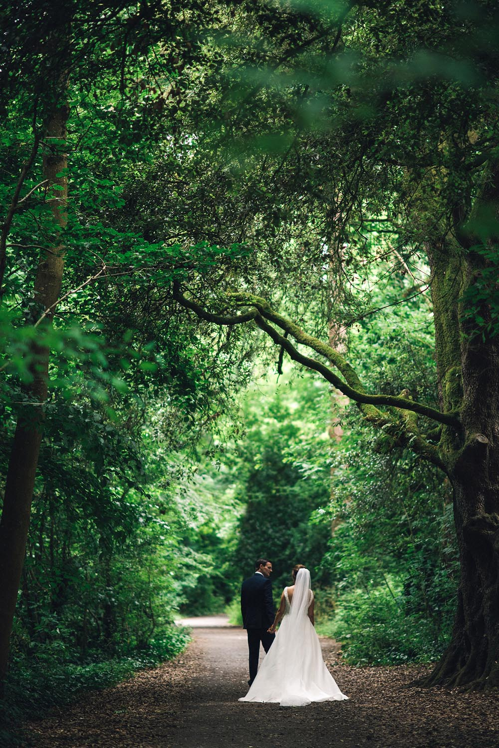 married couple walking in the grounds of Kilkenny Castle on their wedding day