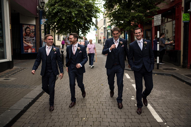 Groomsmen walking through a town