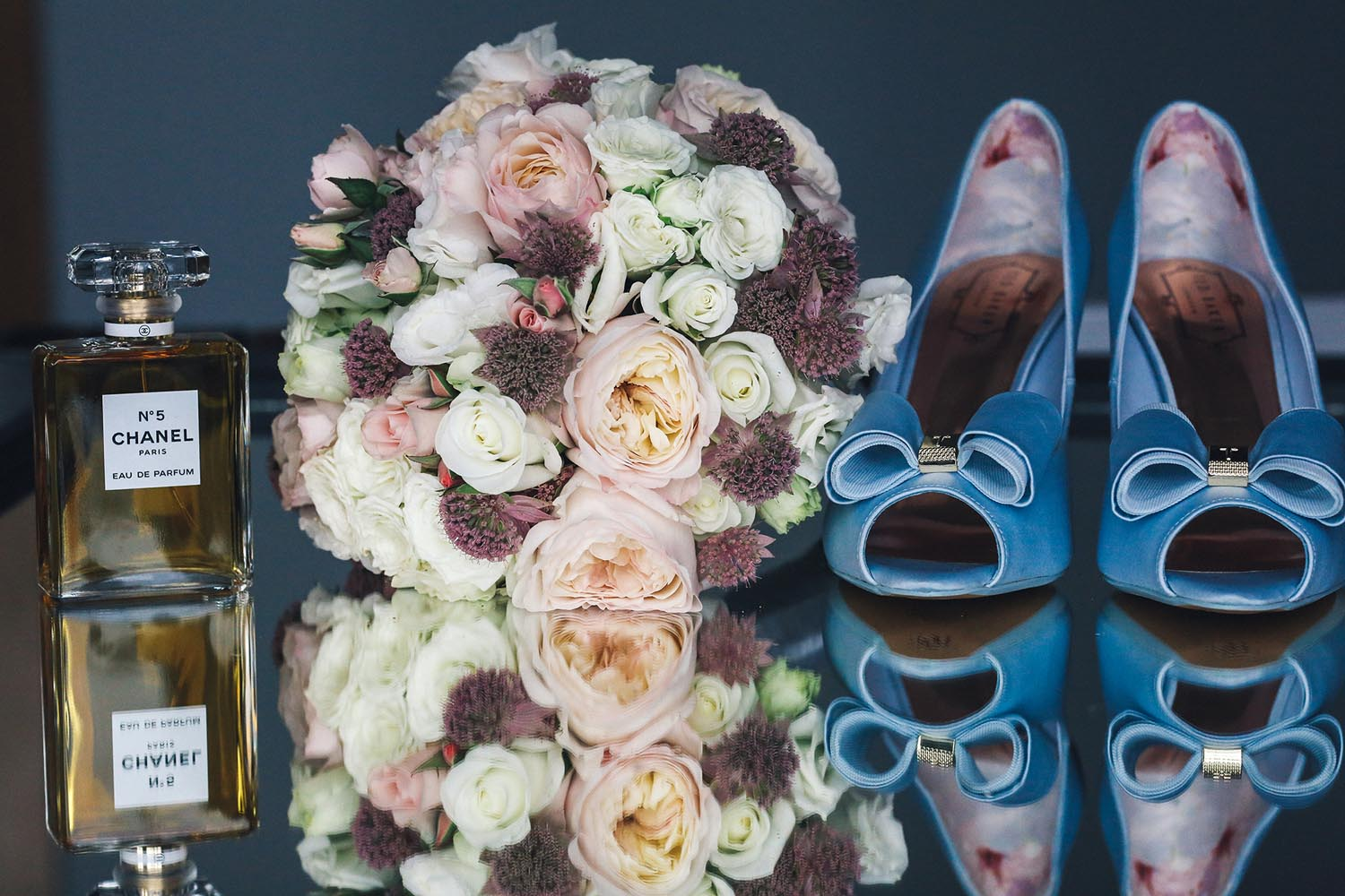 A close up of bridal perfume, bouquet and shoes