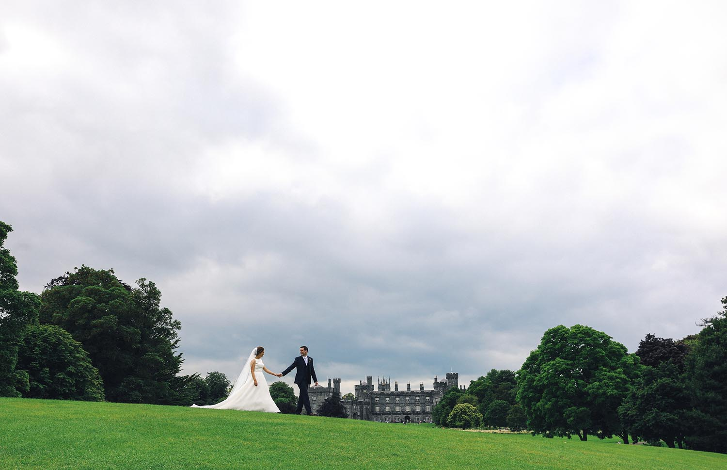 Married couple walking together with Kilkenny Castle in the background