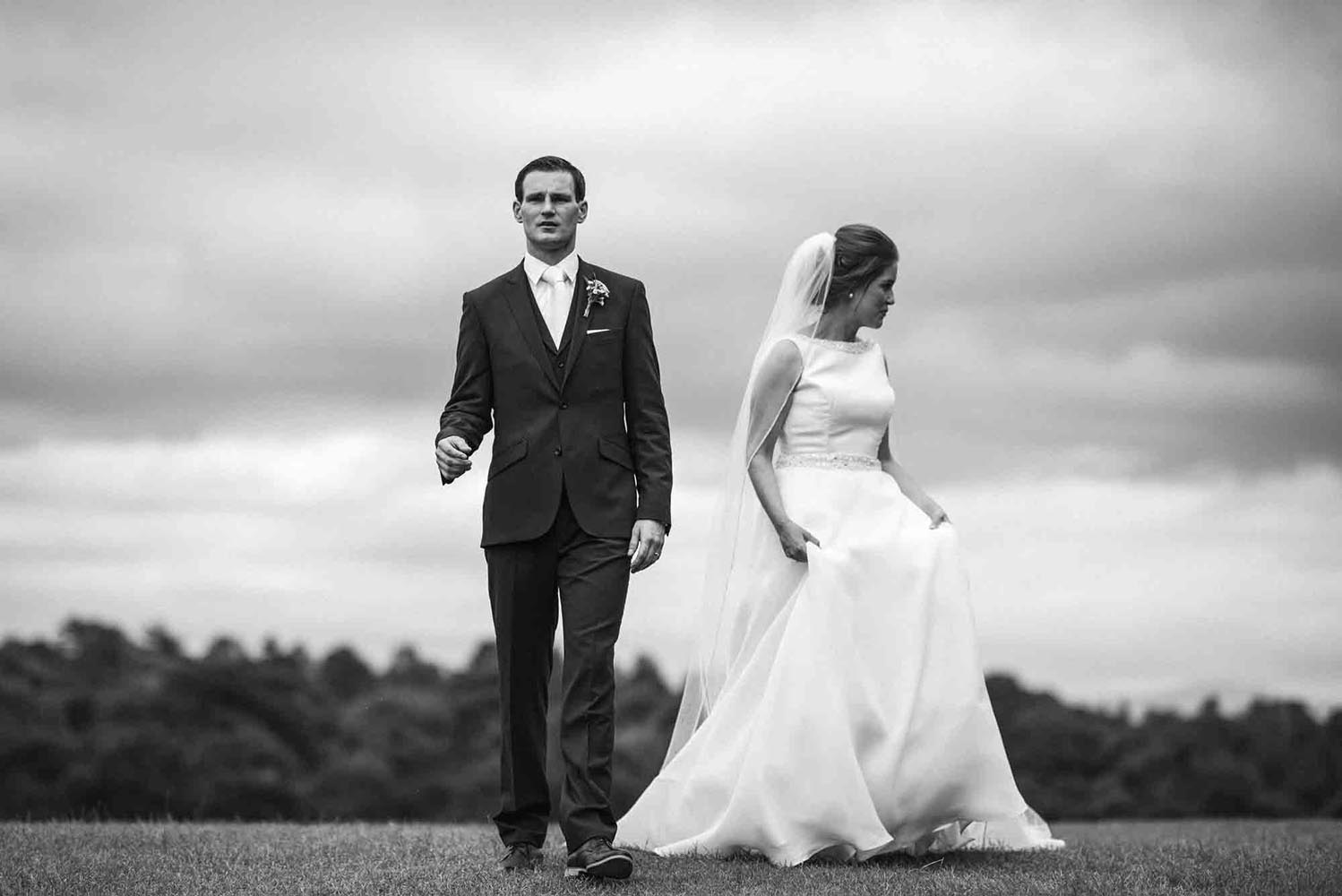 Black and white photo of Groom and bride walking together