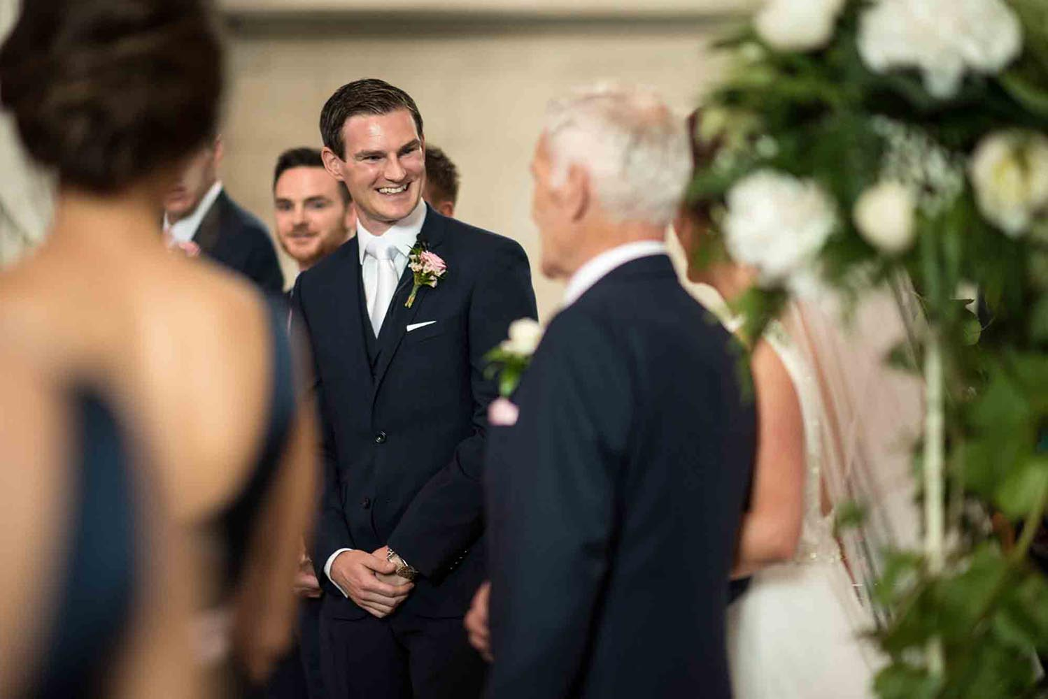 Groom greets his bride at the top of the aisle