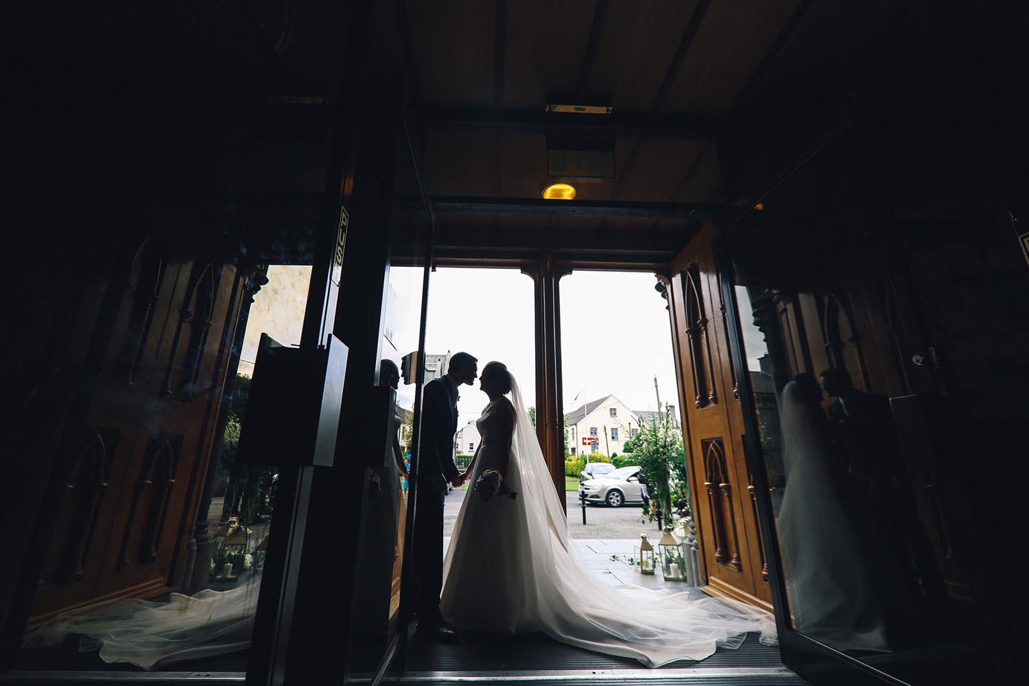 Married couple kiss in church doorway