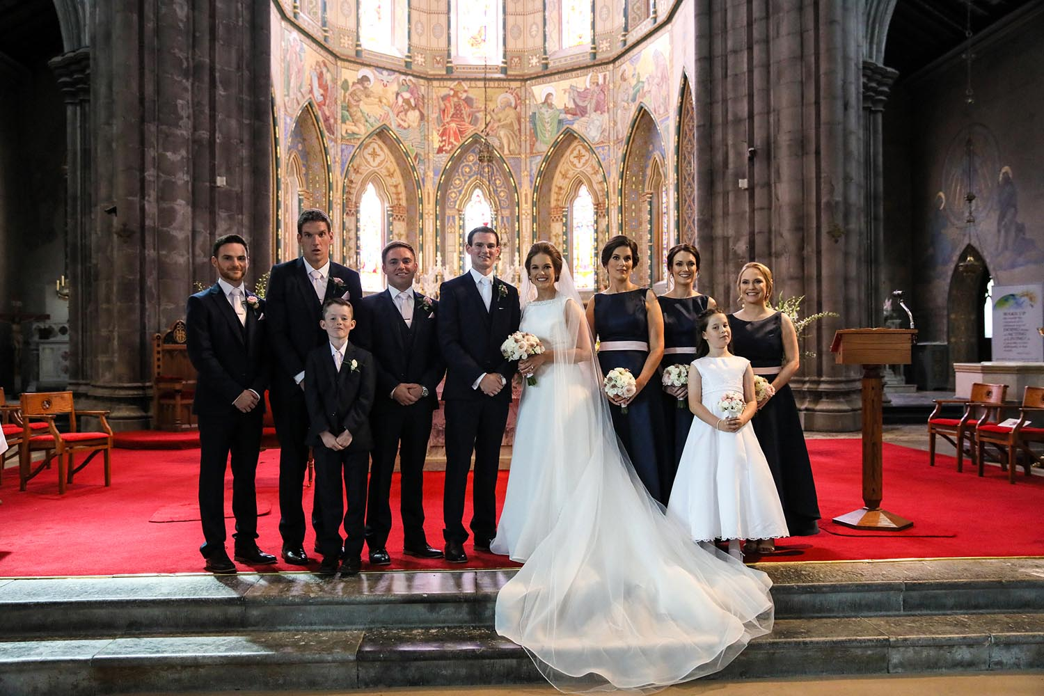 Wedding party standing on the church alter for photographs