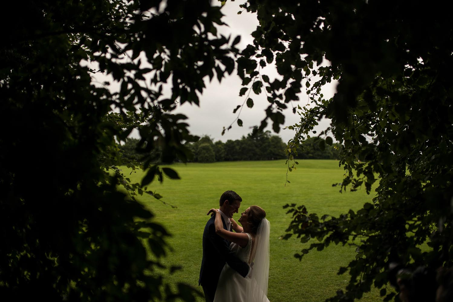 Couple seen kissing through the trees